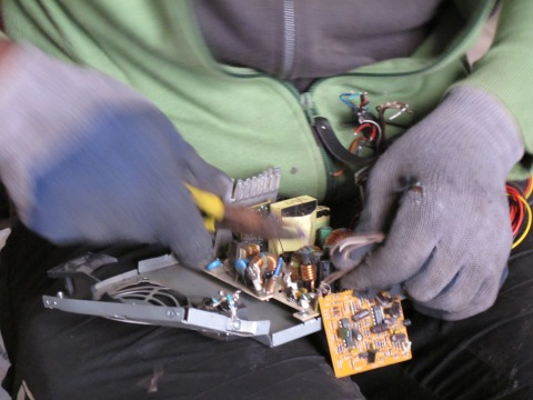 """""""Waste-picker in the squatted warehouse in Barcelona extracting some copper pieces welded in a motherboard"""" CC BY Blanca Callén"""