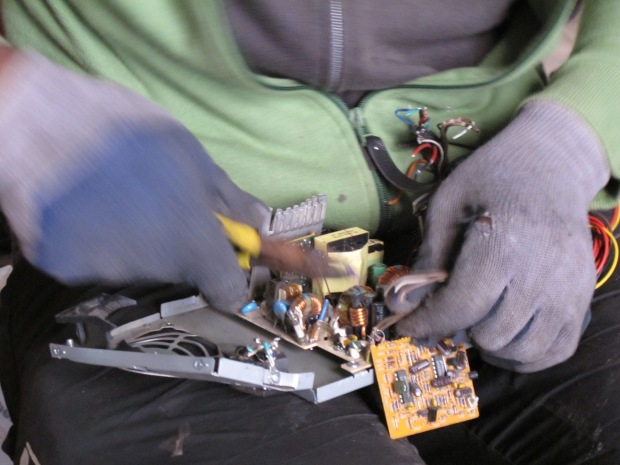 """Waste-picker in the squatted warehouse in Barcelona extracting some copper pieces welded in a motherboard"" CC BY Blanca Callén"